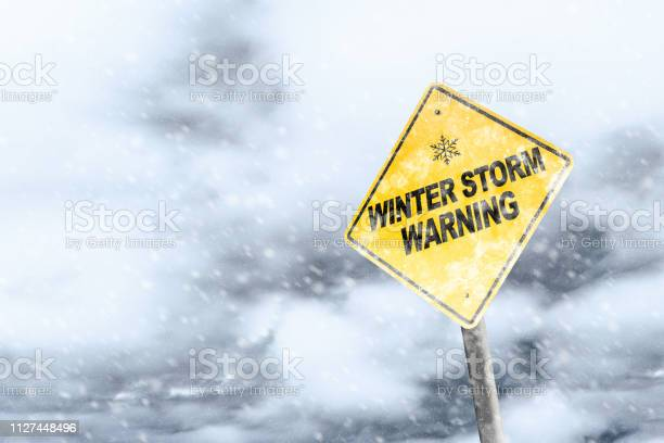 Photo of Winter Storm Warning Sign With Snowfall and Stormy Background