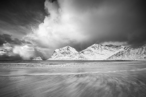 Winter stormy weather at sea and mountains, dramatic clouds and long waves. Northern norwegian landscape. Black and white