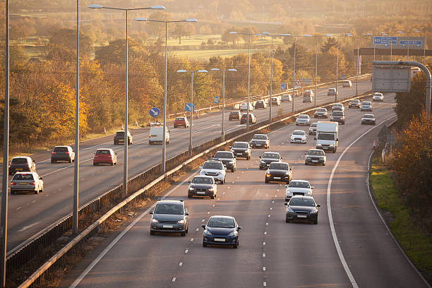 winter sun on sunday motorway traffic Essex England winter sun on sunday motorway traffic Essex England multiple lane highway stock pictures, royalty-free photos & images