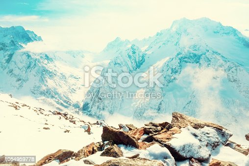 winter sunny day landscape with snow covered peaks of Caucasus mountain, Dombaj over clouds, Russia, toned style
