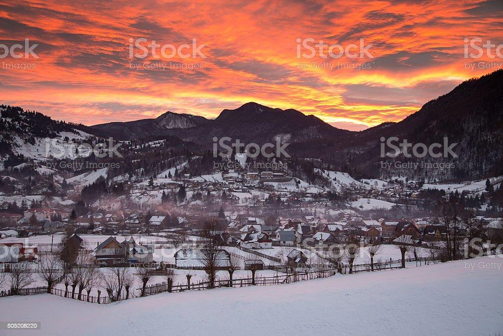 Winter sunrise above the transylvanian village stock photo