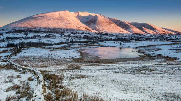 Winter sunrise on Blencathra Blencathra in the northern part of the English Lake District as a winter sun rises and casts reflections into Tewet Tarn northwest england stock pictures, royalty-free photos & images
