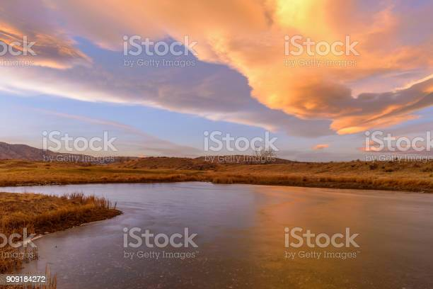 Photo of Winter Sunset Clouds - Colorful sunset clouds rolling over a frozen mountain lake at foothill of front range of Rocky Mountains.