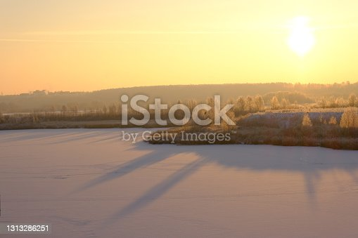 Beautiful winter sunset in nature. The snow-covered surface of the lake, trees and bushes.