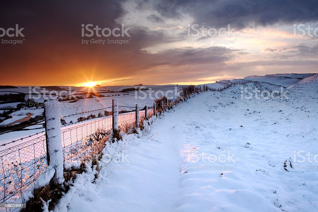Winter Sunset over Maiden Castle in Dorset royalty-free stock photo
