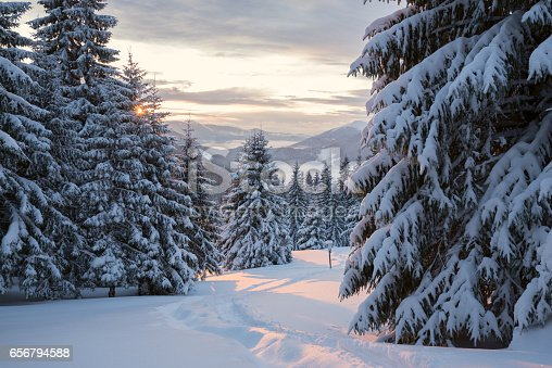 1141614053 istock photo Winter sunset over the forested mountain valley 656794588