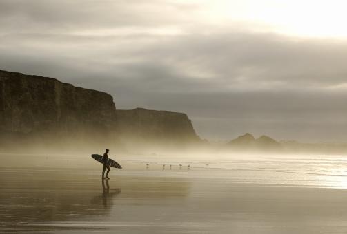 winter surfer walking through mist in cornwall