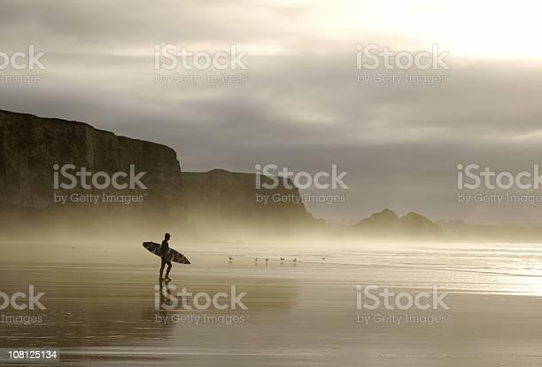 Photo of winter surfer walking through mist in cornwall