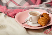 Winter time. A cozy warm pink blanket and a cup of coffee and croissants on the bed.
