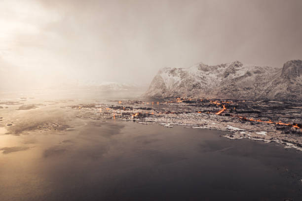 Winter time Lofoten Islands village near fjord. Mountain peaks with snow and cloudy sky. stock photo