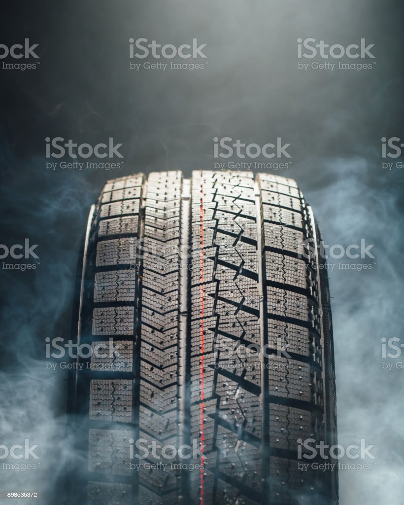 winter tire in smoke, close-up view