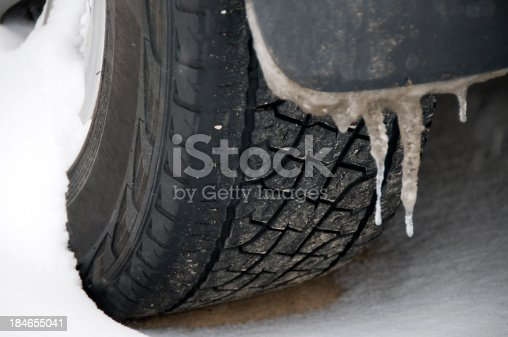 closeup of winter tire in snowstorm with icicles