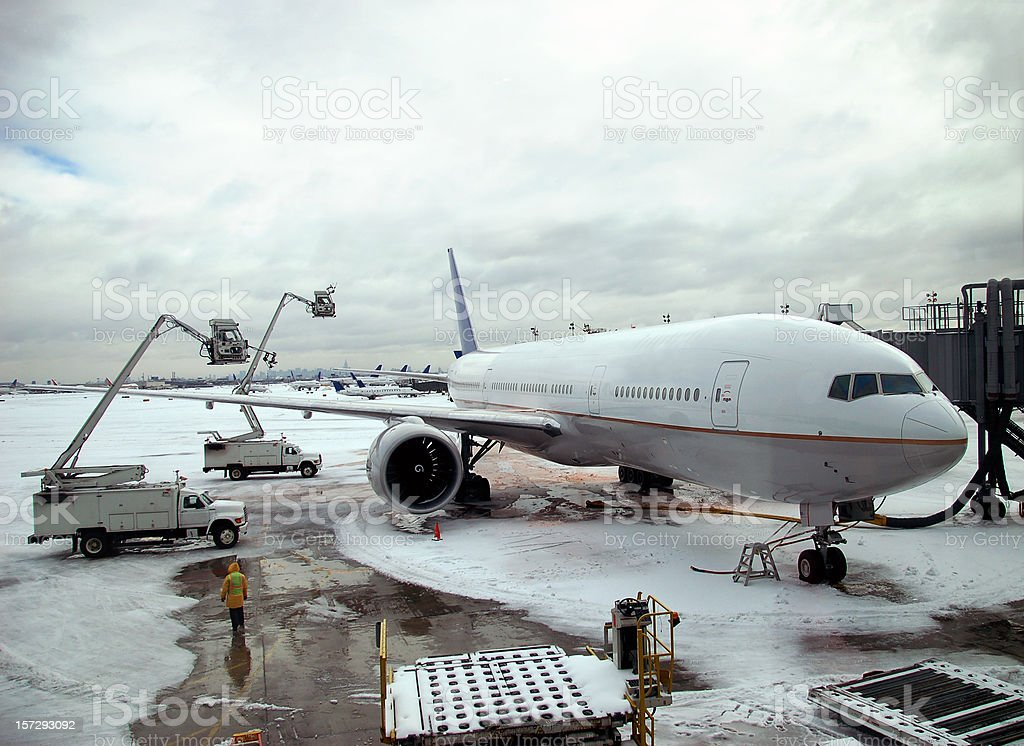 Winter Travel Delay: Airplane getting de-iced during a blizzard / snowstorm stock photo