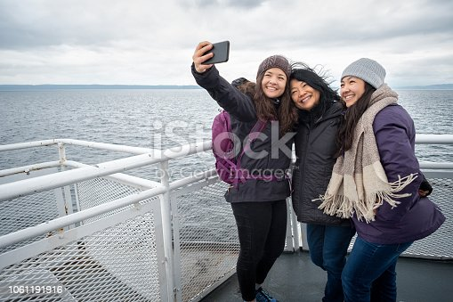 Asian mother and Eurasian teen daughters on deck of ferry between Vancouver and Nanaimo, British Columbia, Canada.