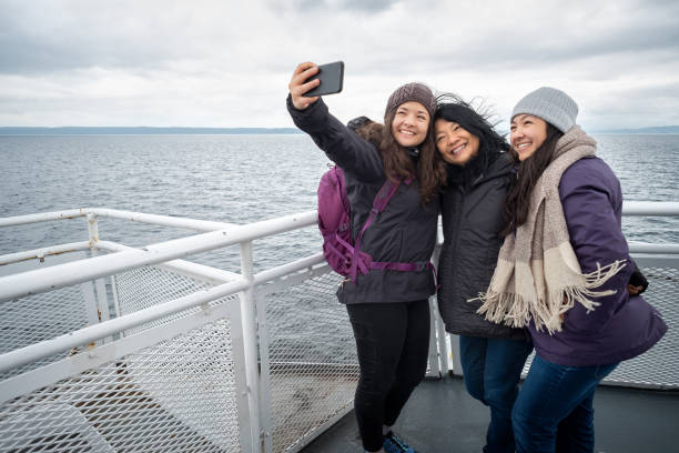 winter travel on ferry, mother and teen daughters taking selfie - ferry imagens e fotografias de stock