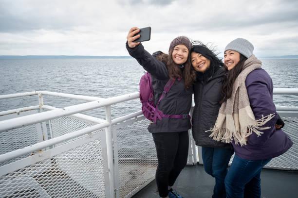 winter reizen op ferry, moeder en tiener dochters selfie te nemen - vancouver canada stockfoto's en -beelden