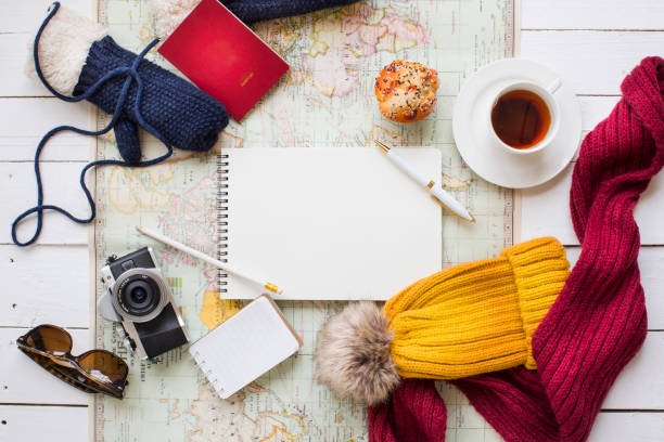 Winter vacation coffee break objects concept image. Winter travel vacation planning, coffee break and related objects on white table top. pasport malaysia stock pictures, royalty-free photos & images
