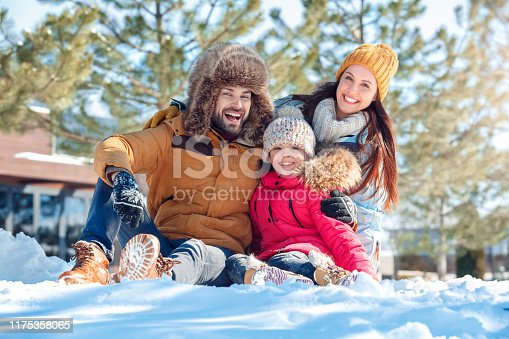 Family on a winter vacation spending time together outdoors sitting hugging loooking camera smiling happy close-up