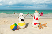 """Subject: A snowman and snow woman tourist couple enjoying winter vacation in a tropical beach.Location: Riviera Maya, Mexico."""