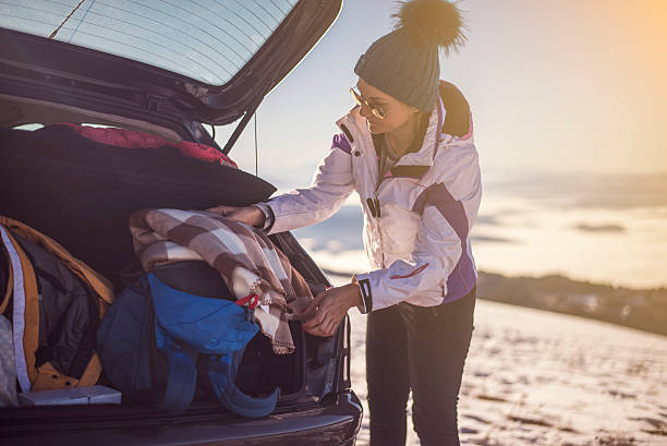 Winter vacation Young woman packing a car trunk and enjoy in the end of great day at the top of mountain. ski holiday stock pictures, royalty-free photos & images