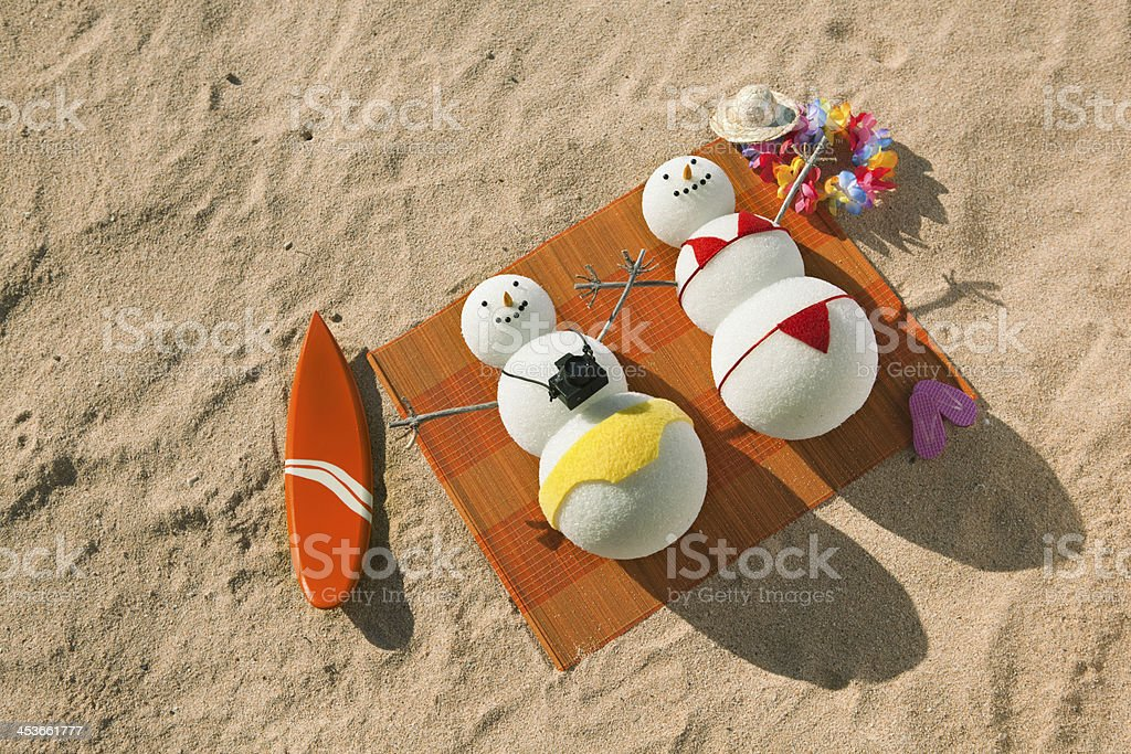 Winter Vacation Snowman Couple Sunbathing on Tropical White Sand Beach royalty-free stock photo