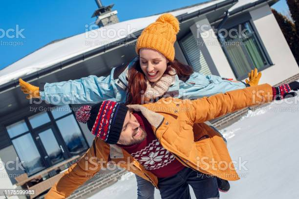 Winter vacation young couple standing together outdoors near house picture id1175599983?b=1&k=6&m=1175599983&s=612x612&h=0ox7k acsvnk nyt6lht67wu fs4w9rb36v8grvanyo=