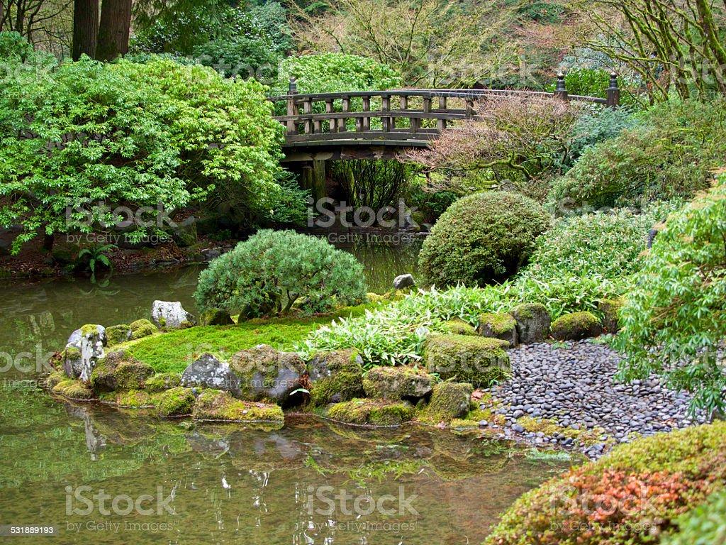 winter view with footbridge across pond japanese garden portland