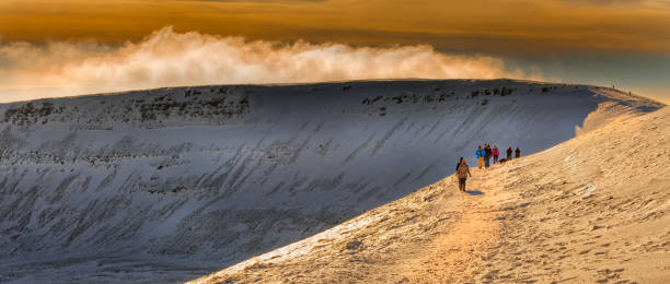 Winter walkers on Penyfan Editorial Brecon Beacons, South Wales, UK - January 19, 2016: Hikers on the approach to Penyfan, the highest mountain in South Wales brecon beacons stock pictures, royalty-free photos & images