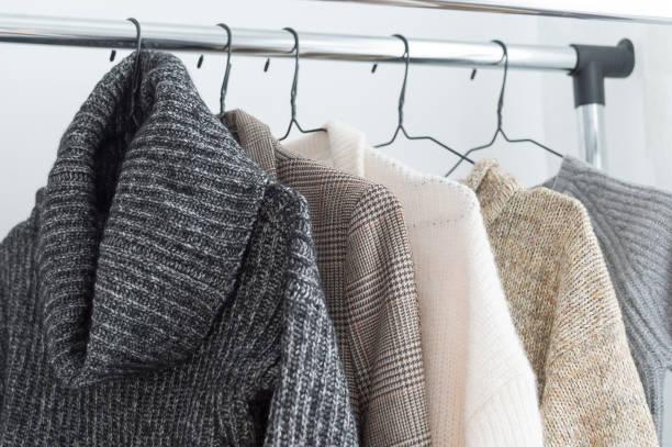 winter-garderobe-schaufenster. weiße und graue ton strick an einen kleiderständer hängen. tiefenschärfe, horizontale - bügelsysteme stock-fotos und bilder