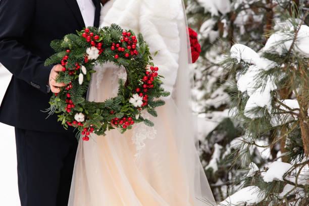 Winter wedding. Bride and groom holding Christmas wreath stock photo