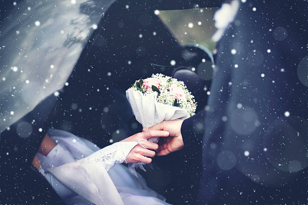 winter wedding couple groom meets bride from car, bouquet flowers - flitterwochen kleid stock-fotos und bilder