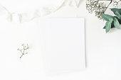 istock Winter wedding desktop stationery mockup. Blank greeting card, baby's breath Gypsophila flowers, eucalyptus branch and silk ribbon. White table background, top view. Christmas flatlay. 1048231430
