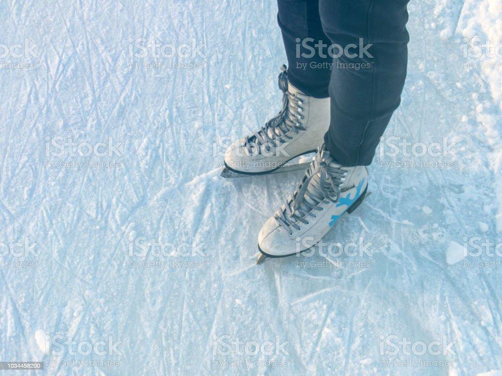 Winter white women\'s ice skates on girl\'s feet on ice