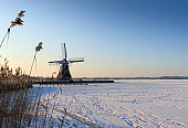 Traditional Dutch windmill at a frozen and snow covered lake.
