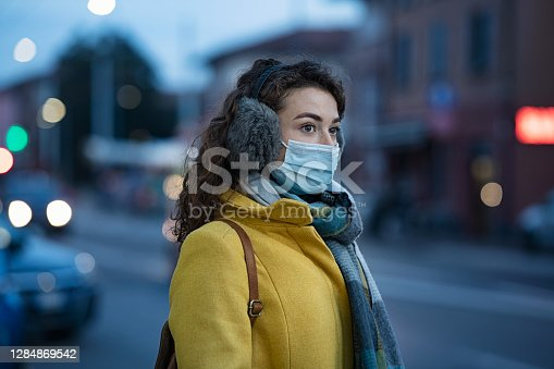 istock Winter woman wearing mask in city street 1284869542