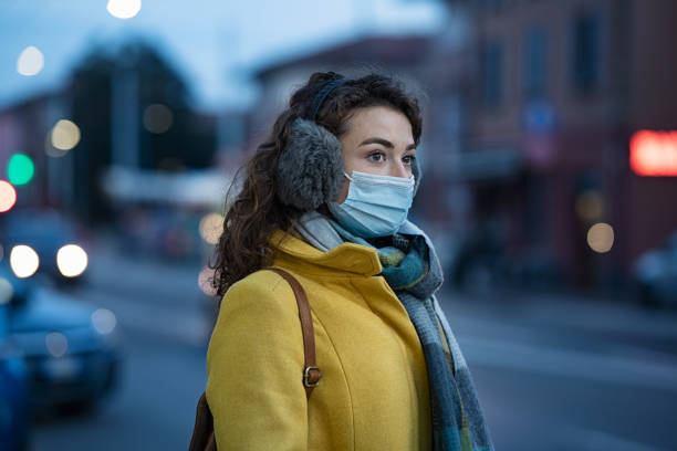 Winter woman wearing mask in city street stock photo