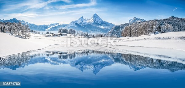 Panoramic view of beautiful white winter wonderland scenery in the Alps with snowy mountain summits reflecting in crystal clear mountain lake on a cold sunny day with blue sky and clouds.