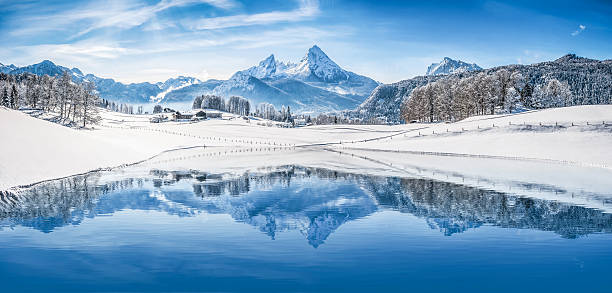 Winter wonderland in the Alps reflecting in crystal-clear mountain lake Panoramic view of beautiful white winter wonderland scenery in the Alps with snowy mountain summits reflecting in crystal clear mountain lake on a cold sunny day with blue sky and clouds. bavarian alps stock pictures, royalty-free photos & images