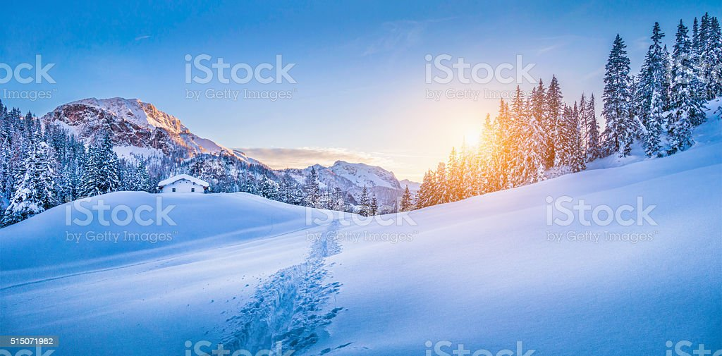 Winter wonderland in the Alps with mountain chalet at sunset stock photo