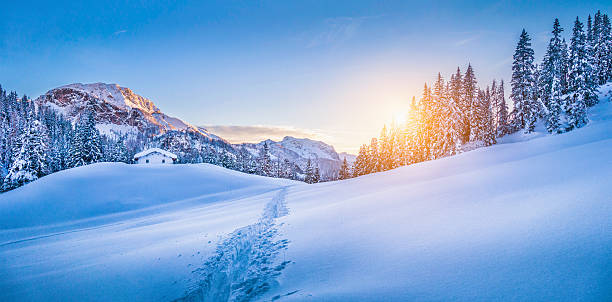 Winter wonderland in the Alps with mountain chalet at sunset Panoramic view of beautiful winter wonderland mountain scenery with traditional mountain cabin the background in the Alps in golden evening light at sunset. chalet stock pictures, royalty-free photos & images