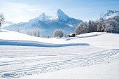 Beautiful winter wonderland mountain scenery in the Alps with cross country skiing track on a scenic cold sunny day with blue sky and clouds