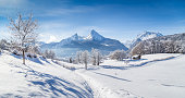 Beautiful winter scenery with trees and mountain tops in the Alps on a sunny day with blue sky and clouds.