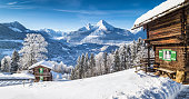 Panoramic view of beautiful winter wonderland mountain scenery in the Alps with traditional mountain chalets on a cold sunny day with blue sky and clouds.