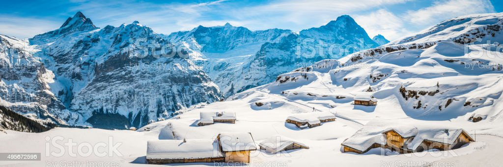 Winter wonderland wooden ski chalets Alpine village snowy mountain peaks stock photo