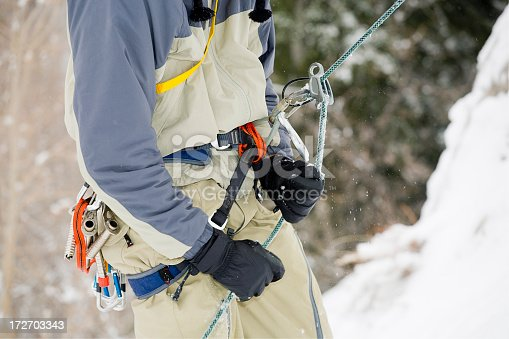 A close-up of the harness of an ice climber in winter.