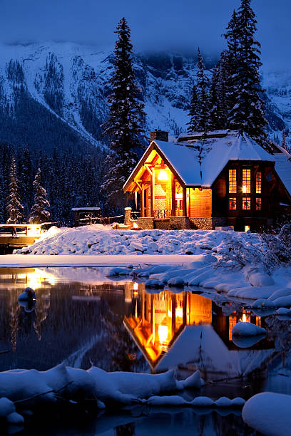 Wintery Cabin Reflection Wintery Cabin Reflection at Emerald Lake Lodge in Yoho National Park, British Columbia, Canada emerald lake stock pictures, royalty-free photos & images