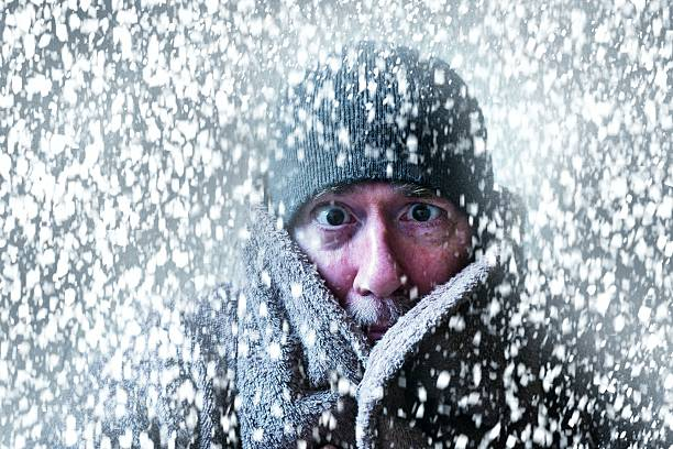 Wintery scene of a man shivering in a snow storm Wintery picture of a very cold man with a XMAS vibe warm clothing stock pictures, royalty-free photos & images