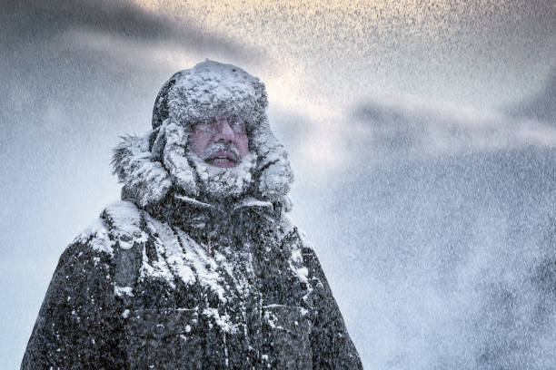 wintery scene of a man with furry and full beard shivering in a snow storm - weather stock photos and pictures