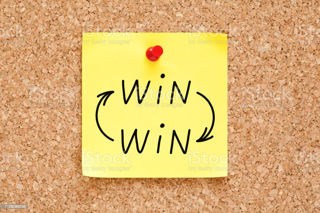 Win-Win Arrows Concept On Sticky Note Win-Win arrows concept handwritten on yellow sticky note pinned on bulletin cork board. Adhesive Note Stock Photo