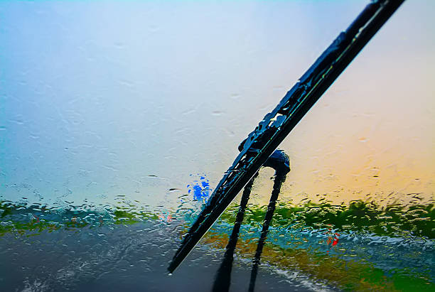 wiper on a wet windshield wiper on a wet windshield at sunset windshield wiper stock pictures, royalty-free photos & images